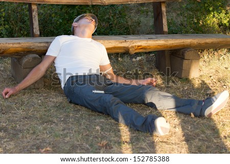 Heroin user lying down leaning on a bench in the park experiencing a state of relaxation and euphoria - stock photo