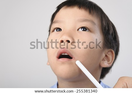 Herpes on kid mouth point by white stick - stock photo