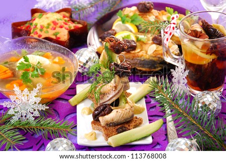herring appetizer with prune and gherkin and other traditional polish dishes on christmas table - stock photo