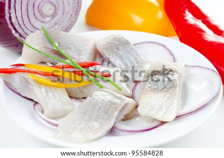 Herring bites on a plate with vegetables red yellow pepper and onion - stock photo
