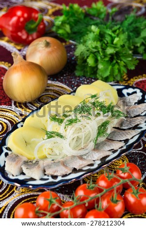 Herring, cooked potatoes, onions and herbs. - stock photo