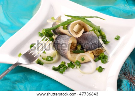 herring fillets with chive on white plate