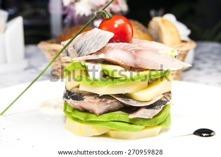 Herring salad with avocado sauce on a plate in a restaurant - stock photo