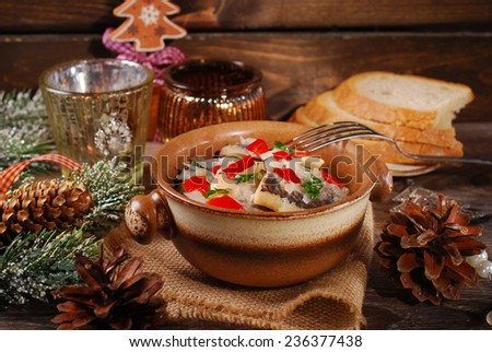 herring salad with onion,red pepper and oil for christmas served in rustic style on wooden table  - stock photo