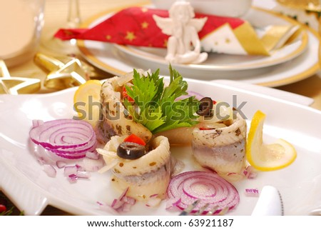 herring  salad with paprika, olives and red onion on christmas table - stock photo