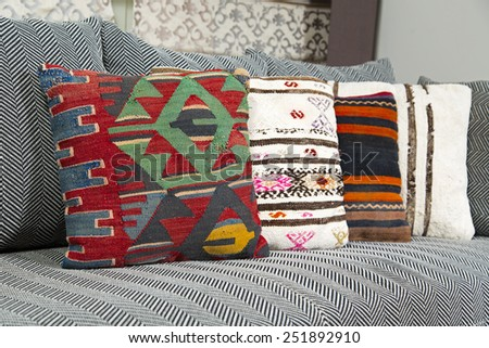 Herringbone sofa with traditional Turkish handmade colorful natural fabric pillows - stock photo