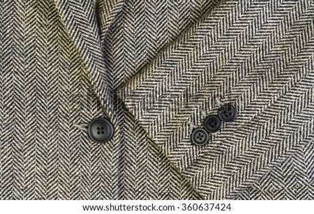 Herringbone tweed women jacket with closeup on wool fabric texture with buttons - stock photo