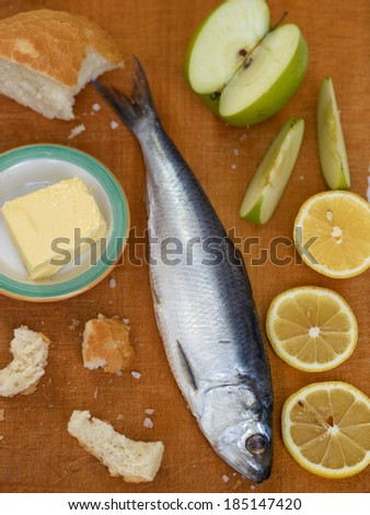 Herrings on a wooden background with lemon, apple, salt  with selective focus - stock photo