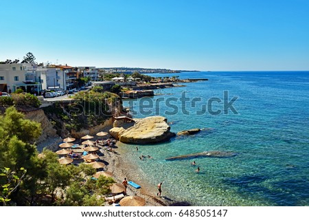 Hersonissos, Greece - July 14, 2016: Many people enjoy a summer day at the beach of Hersonissos on the island of Crete in Greece.
