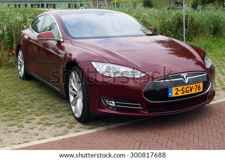 Herwijnen, The Netherlands - July 24, 2015: : Multi-coat Red Electric Tesla Motors Model S parked on a public parking lot. Tesla Motors is an American automotive company. - stock photo