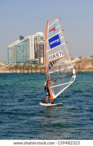 HERZLIYA,ISR- OCT 06:Israeli wind surfer surf along Herzliya Pituah skyline on Oct 06 2009.Windsurfing is one of Israel's most successful olympic sports.