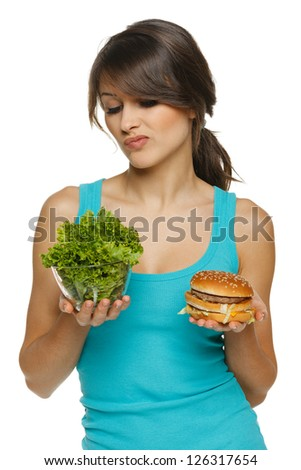 Hesitating woman making decision between healthy salad and fast food, over white background - stock photo