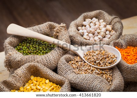 Hessian bags with dry peas, chick peas, red lentils, wheat and green mung on kitchen table - stock photo