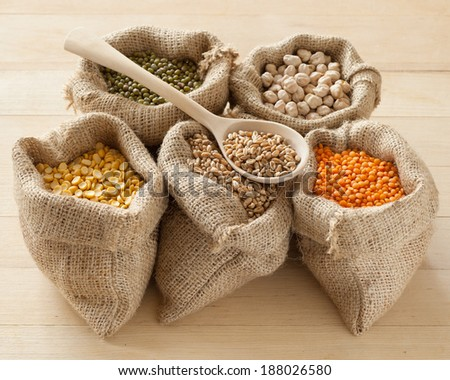 hessian bags with peas, chick peas, red lentils, wheat and green mung on table - stock photo