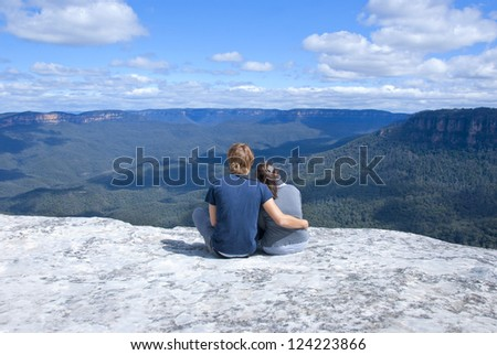 Hetero couple enjoying scenic view of blue mountains near Sydney, New South Wales, Australia, while sitting on top of rock next to edge.