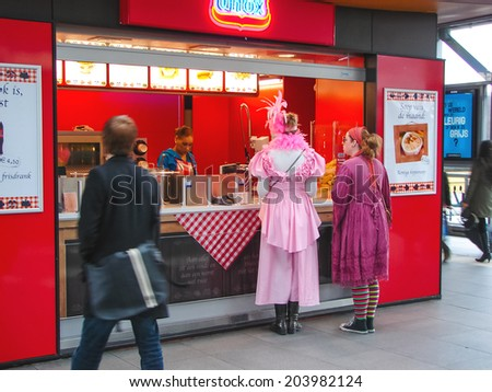 HEUSDEN,THE NETHERLANDS - FEBRUARY 18, 2012 : Girls in carnival costumes near the cafe fast food in town of Heusden. In many Dutch cities have annual winter carnivals - stock photo