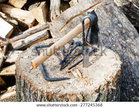 hew axe and forged hardware on wooden block near village smithy