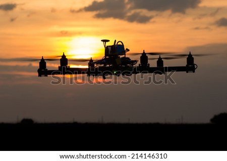 Hexacopter drone flying in the sunset - stock photo