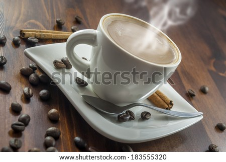 hhot cup of coffee and cinnamon on wood table