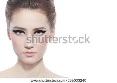 Hi-key portrait of young beautiful girl with stylish cat eye make-up over white background - stock photo