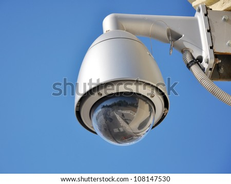Hi-tech dome type camera and a blue sky - stock photo