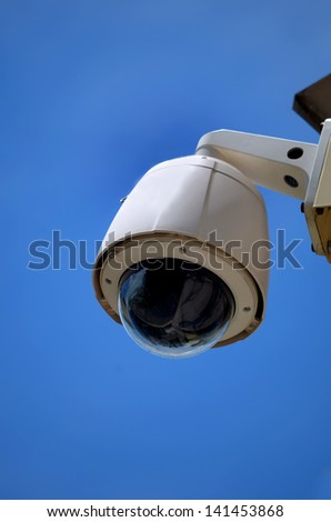 Hi-tech dome type camera on a blue sky - stock photo