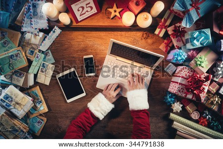 Hi-tech Santa Claus working at his desk and typing on a laptop surrounded by gift boxes and Christmas letters, hands top view - stock photo