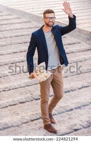 Hi there! Full length of cheerful young man in smart casual wear holding bouquet of flowers and waving hand to someone while walking by the street  - stock photo