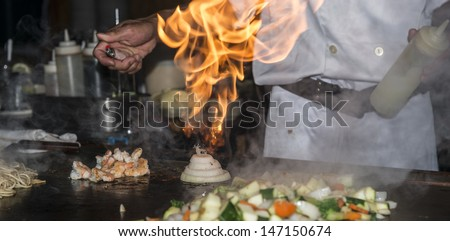 Hibachi teppanyaki style table food preparation in a Japanese steakhouse - stock photo