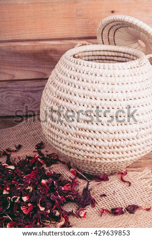 Hibiscus in a basket on a wooden background