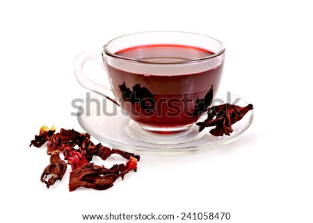 Hibiscus tea in a glass cup, dry petals isolated on white background