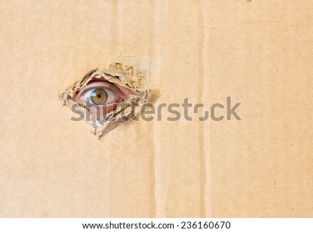 Hidden eye spying through torn hole in cardboard paper - stock photo