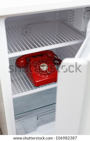 Hidden vintage British red phone in a fridge