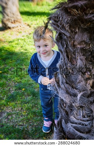 Hide and seek. Little handsome boy emerging from behind a tree in park. - stock photo