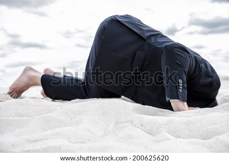 Hiding from his problems. Barefoot man in formalwear hiding his head in sand - stock photo