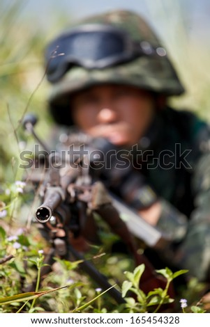 Hiding soldier aimed gun to target - stock photo
