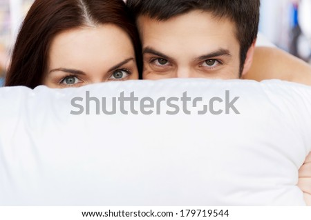 Hiding their faces behind the pillow. Cheerful young loving couple lying in bed and looking out of the pillow - stock photo