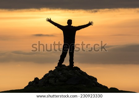 High achiever, silhouette of a man on top of a mountain - stock photo