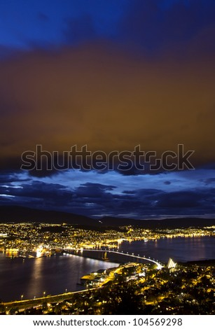 High aerial view over Tromso at night - the mainland (Tromsdalen) and the city central island (Troms�¸ya) and the glowing clouds on to of the city, reflecting the city lights. - stock photo