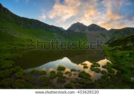 High altitude alpine lake in idyllic land once covered by glaciers. Majestic rocky mountain peak glowing at sunset. Wide angle vertical shot taken on the Italian Alps at 2300 m asl. - stock photo