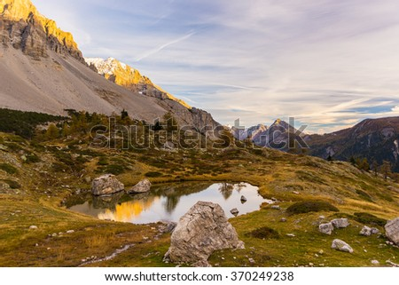 High altitude alpine lake in idyllic land once covered by glaciers. Reflection of snowcapped mountain range and scenic colorful sky at sunset. Wide angle shot taken on the Italian Alps at 2200 m asl. - stock photo