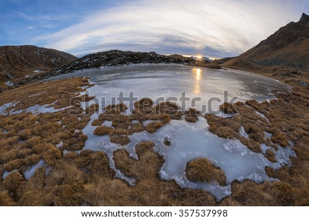 High altitude alpine lake in idyllic land. Reflection of the sunlight on the frozen surface. Glowing sunstar at the horizon at sunset. Ultra wide angle fisheye on the Italian Alps at 2500 m asl. - stock photo
