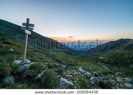 High altitude alpine landscape at dawn with footpath signposts. Location: Orsiera Regional Park, Piedmont, Italy. - stock photo