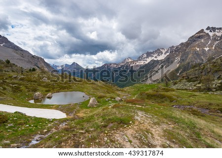 High altitude alpine pond in extrem terrain rocky landscape once covered by glaciers. Dramatic stormy sky and snowcapped mountain range, Italian French Alps. - stock photo