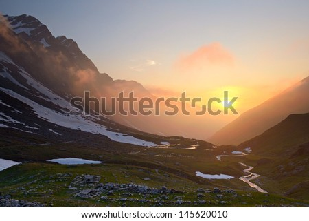 High altitude alpine valley at sunset in stormy weather. Location: western Alps, Torino Province, Italy. - stock photo