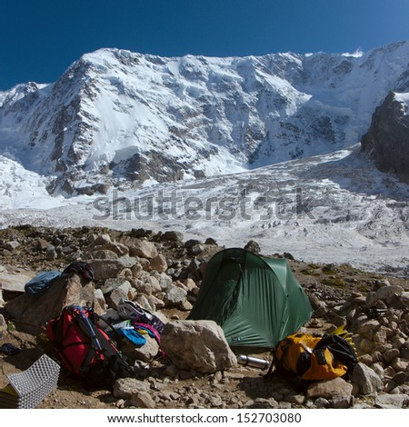 High altitude bivouac with tent, backpack and mountaineering gear with mountains with snow and glaciers in the background
