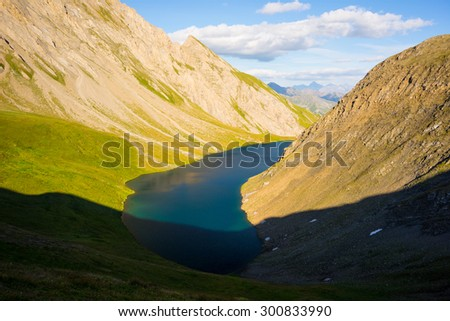 High altitude blue lake in idyllic uncontaminated environment once covered by glaciers. Summer adventures and best trekking destination in Valle d'Aosta, Italian Alps. Wide angle view at sunset. - stock photo