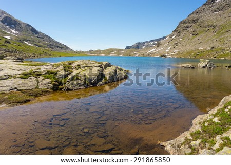 High altitude blue lake in idyllic uncontaminated environment with clean and transparent water. Summer adventure in the Italian French Alps. Wide angle view. - stock photo