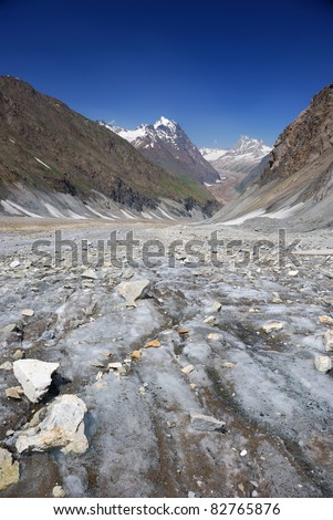 High altitude mountains landscape view with cracked rocks on the surface of glacier. - stock photo