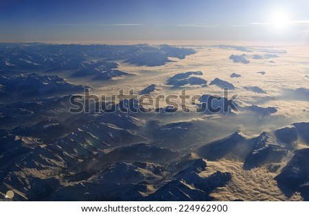 High altitude view of sunset over the mountains and the cloud layer. The Italian Dolomites.  - stock photo